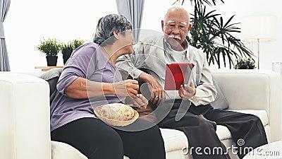 Homem superior asiático que usa o tablet pc e lãs de confecção de malhas do ofício superior da mão da mulher em casa video estoque