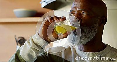 Homem superior que bebe um vidro do suco na cozinha 4k filme