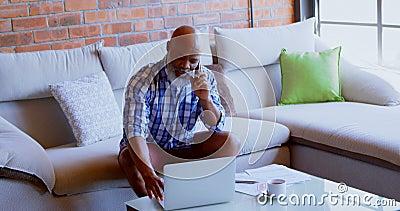 Homem superior que usa o portátil ao falar o telefone celular do OM na sala de visitas 4k filme