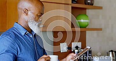 Homem superior que usa a tabuleta digital ao comer o café preto na cozinha 4k vídeos de arquivo
