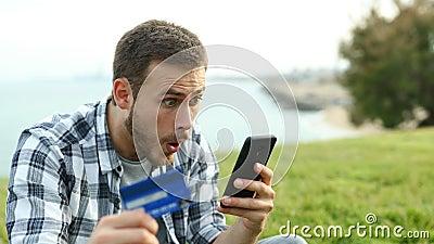 Homem surpreso pagando com cartão de crédito e telefone video estoque