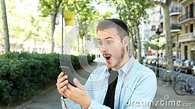 Homem surpreso usa um telefone e olha para a câmera filme