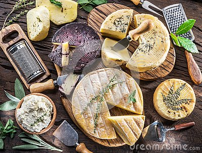 Homemade cheeses on the wooden background. Stock Photo