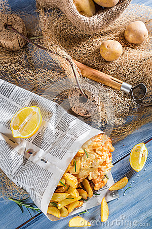 Homemade fish and chips in newspaper with lemon for Fish and chips newspaper