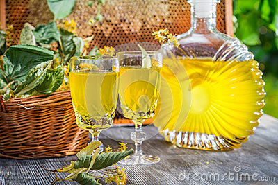 Homemade liqueur made of honey and lime in summer garden on old wooden ...