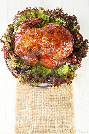 Homemade smoked whole chicken on leaf lettuce