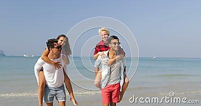 Homens Carry Women On Back, dois pares andando em turistas de fala dos povos alegres felizes da praia em férias video estoque