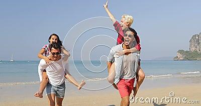 Homens Carry Women On Back, dois pares que correm em turistas alegres felizes dos povos da praia em férias video estoque