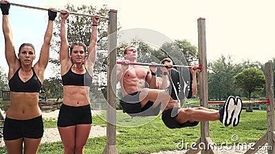 Homens e mulheres que fazem vários exercícios do peso do corpo na barra horizontal vídeos de arquivo
