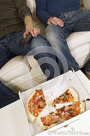Homens que olham a tevê com pizza comida metade na tabela