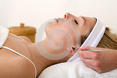 Homeopath applying auriculotherapy techniques.
