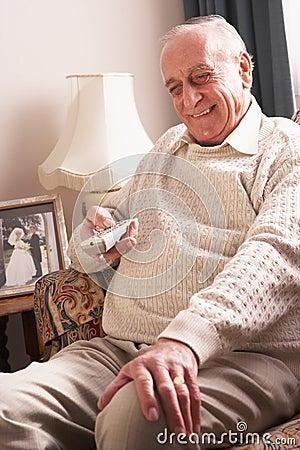 Homme aîné regardant la TV à la maison