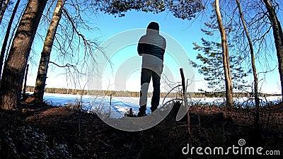 Homme appréciant le beau paysage 4K du lac congelé avec la lumière du soleil par les bois de pin de bouleau banque de vidéos