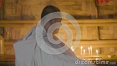 Homme asiatique dans le temple authentique tandis que rituel de religion sur le fond brûlant de bougie Espoir heureux d'homme sur banque de vidéos