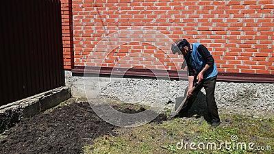 Homme avec du chiffon sur son chef, creusant la terre avec la pelle, près de la haute barrière de brique clips vidéos