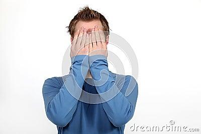 Homme couvrant son visage