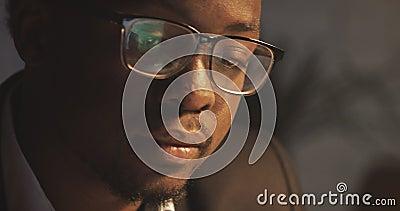 Homme d'affaires concentr? d'Afro-am?ricain dans des lunettes devant l'ordinateur portable avec la r?flexion de l'affichage dans  clips vidéos