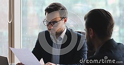Homme d'affaires confiant en lunettes discutant des détails du contrat avec son partenaire banque de vidéos