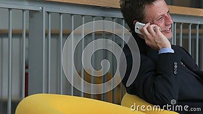 Homme d'affaires parlant au téléphone se reposant sur un voyage d'affaires banque de vidéos