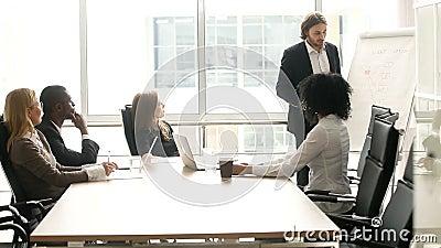 Homme d'affaires présentant l'exposé au groupe multi-ethnique de clients lors de la réunion de bureau banque de vidéos