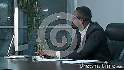 Homme d'affaires réussi d'afro-américain s'asseyant au bureau, travaillant à l'ordinateur portable générique, introduisant un mes banque de vidéos