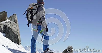 Homme d'alpiniste de grimpeur atteignant le dessus neigeux de bâti avec la hache de glace dans le jour ensoleillé Activité de ski banque de vidéos