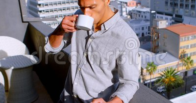 Homme employant le mobile tout en ayant le café dans le balcon 4k banque de vidéos