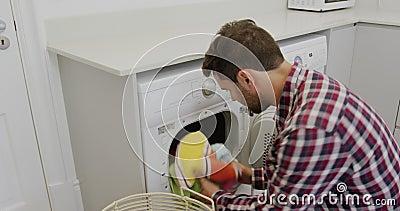 Homme enlevant des tissus de la machine à laver dans une maison confortable 4k clips vidéos