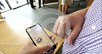 Homme examinant la nouvelle caractéristique de la bande APP de l'AR dans l'iPhone XS clips vidéos
