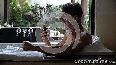 Homme fâché utilisant Smartphone tout en se situant dans la baignoire dans la salle de bains L'homme a reçu un mauvais message et banque de vidéos