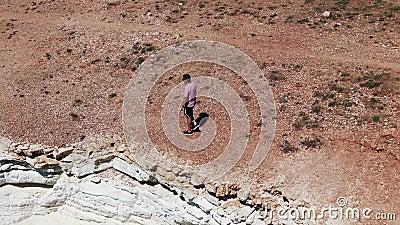 Homme habillé en bref, des espadrilles et un T-shirt marchant le long d'une falaise Vagues mousseuses frappant le rivage rocheux  clips vidéos