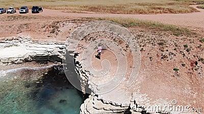 Homme habillé en bref, des espadrilles et un T-shirt marchant le long d'une falaise Vagues mousseuses frappant le rivage rocheux  banque de vidéos