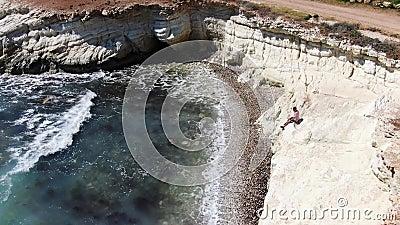Homme habillé en bref, des espadrilles et un T-shirt se reposant sur une falaise Vagues mousseuses frappant le rivage rocheux Tir banque de vidéos