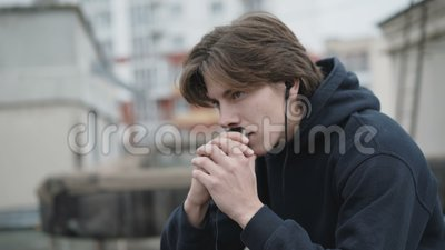 Homme libre écoutant pensivement la musique dans des écouteurs sur un toit banque de vidéos