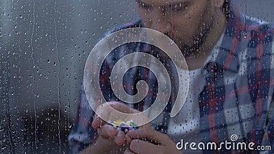 Homme malade déprimé tenant la pleine paume du médicament, se reposant derrière la fenêtre pluvieuse banque de vidéos