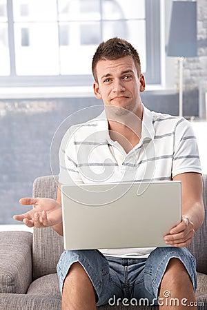 Homme malheureux avec l ordinateur portatif à la maison