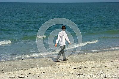Homme marchant le long de la plage