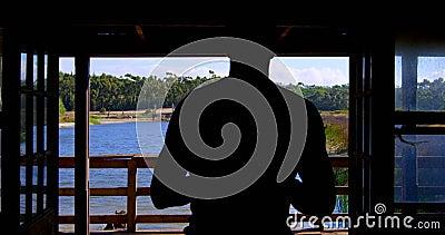 Homme marchant vers le balcon à la maison 4k banque de vidéos