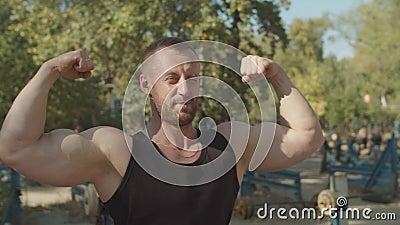 Homme musculaire brutal debout dans la pose double biceps banque de vidéos