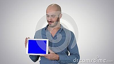 Homme occasionnel souriant présentant une tablette avec un écran vierge sur fond de dégradé banque de vidéos
