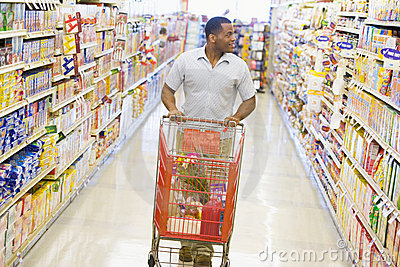 Homme poussant le chariot le long du bas-côté de supermarché