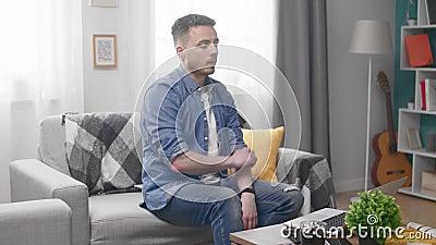 Homme s'asseyant sur le sofa et finition travaillant à l'ordinateur portable banque de vidéos