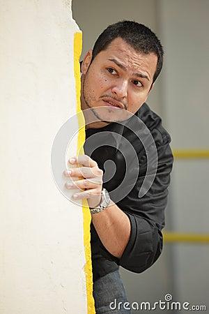 Homme se cachant derrière un mur