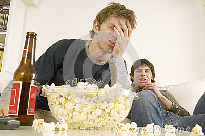 Hommes bouleversés regardant la TV avec le maïs éclaté et la bière sur le Tableau