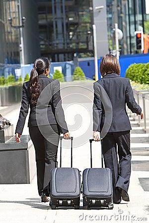 Hommes d affaires en voyage de femmes avec des valises de roulement