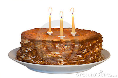 Honey cake with lighting candles