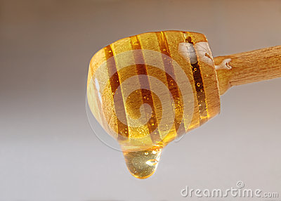 Honey dripping from a wooden honey