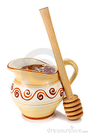 Honey in a jug and wooden stick