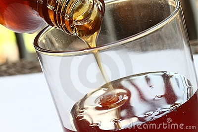 Honey pouring from jar
