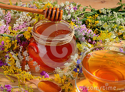 Honey in glass jar close up with wooden spoons on flowers background.